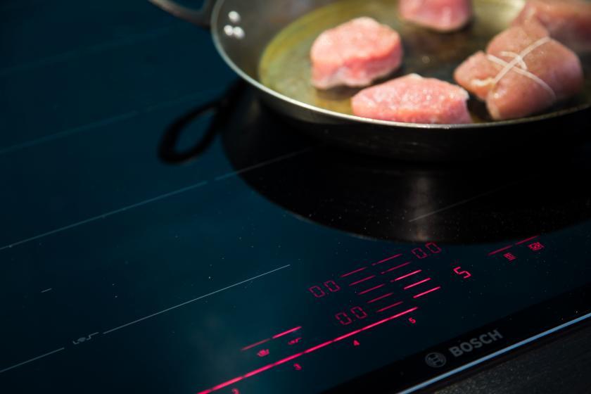 Schweinemedaillons werden in einer Pfanne gebraten.