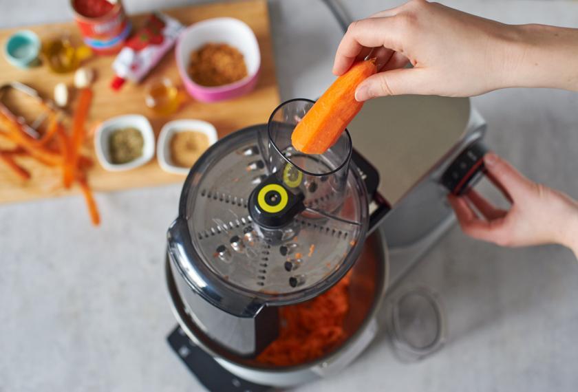 Für die schnelle Tomatensoße wird eine Möhre mit einer Küchenmaschine geraspelt.