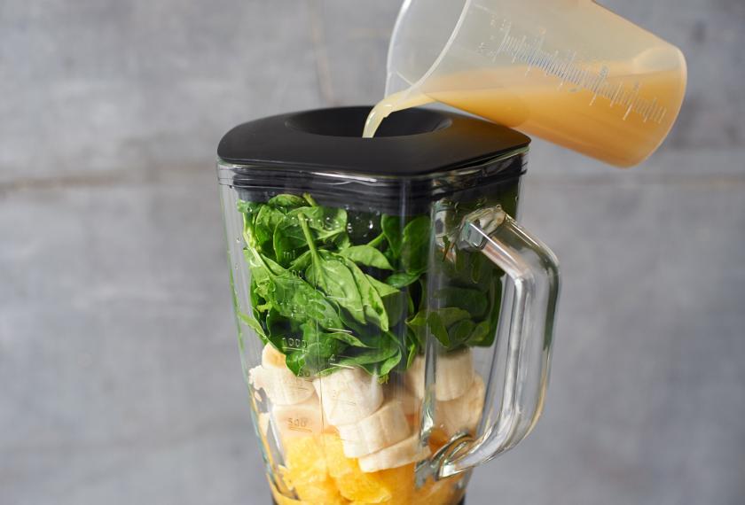 Für doe Smoothie Bowl mit Bananen wird Saft in den gefüllten Mixer gegossen.
