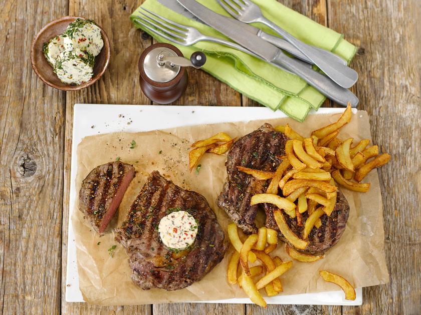 Steak mit Pommes frites auf Backpapier und einem Teller angerichtet. Dazu Kräuterbutter.