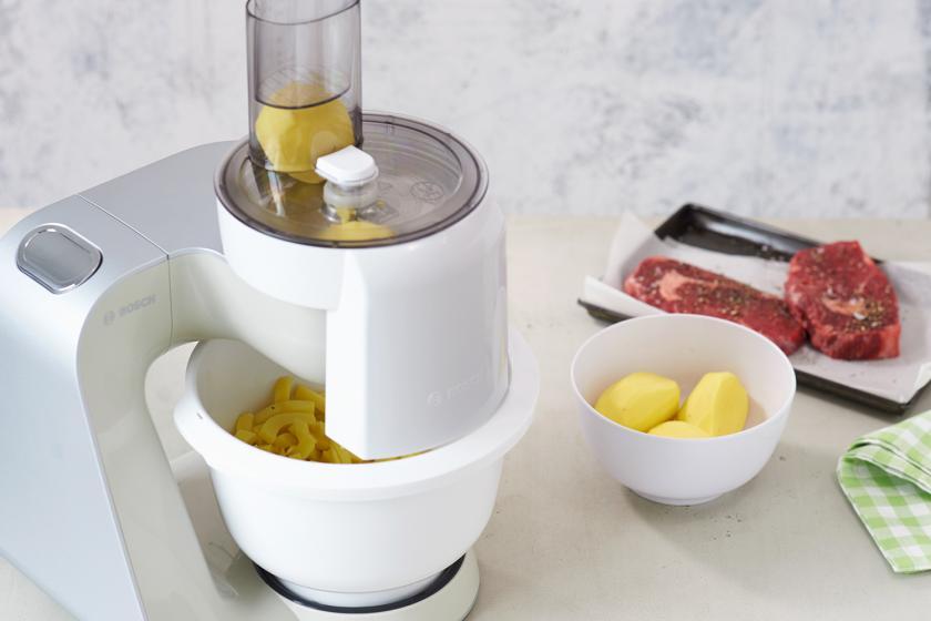 Für Steak mit Pommes frites werden Kartoffeln mit einem Küchengerät in Pommes geschnitten.