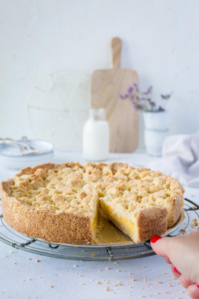 Angeschnittener Streuselkuchen mit Pudding auf Kuchengitter.