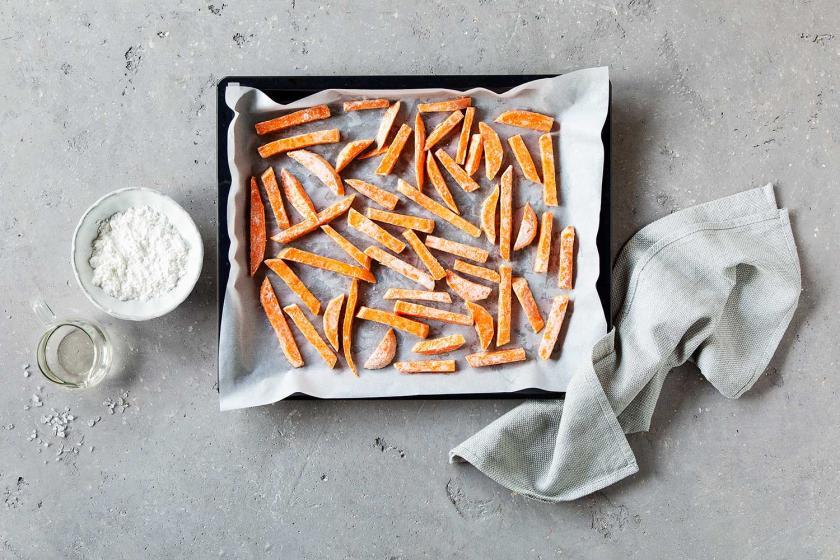 Süßkartoffel-Pommes mit Stärkemantel auf einem Backblech.