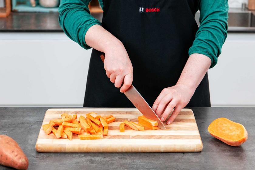 Süßkartoffel wird auf einem Brett in Süßkartoffel-Pommes geschnitten.