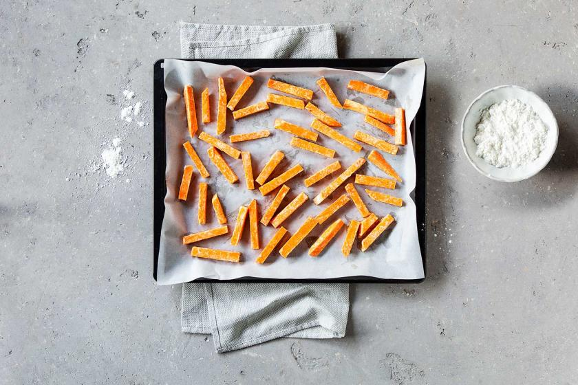 Süßkartoffel-Pommes mit Stärke ummantelt auf einem Backblech.