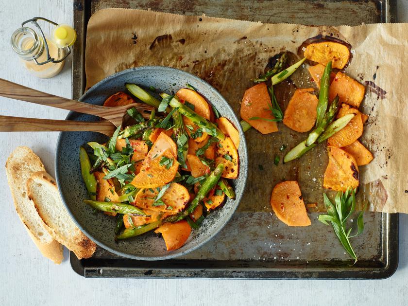 Süßkartoffelsalat ist auf einem Teller angerichtet und steht auf einem Backblech mit restlichem Salat darauf.