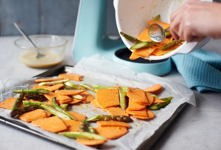 Gemüse für den Süßkartoffelsalat wird auf einem Backblech verteilt.