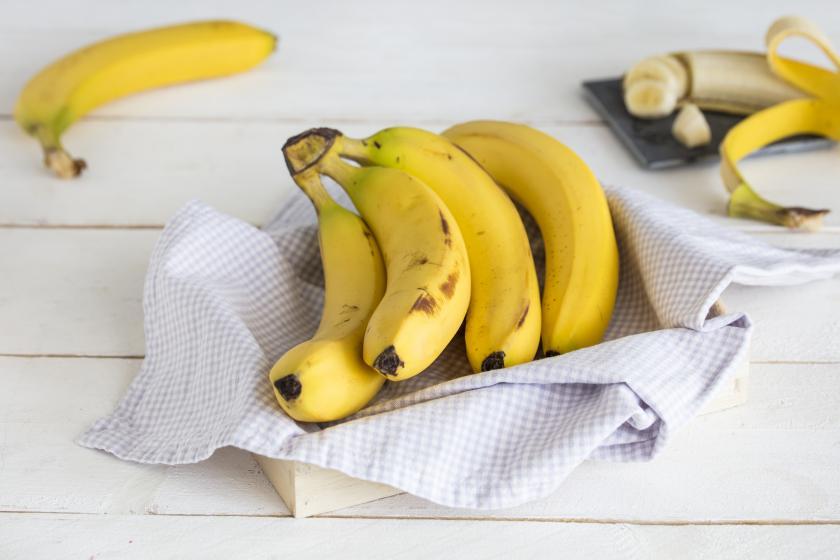 Eine Bananenstaude liegt in einem Korb mit Tuch auf einer Holzfläche.
