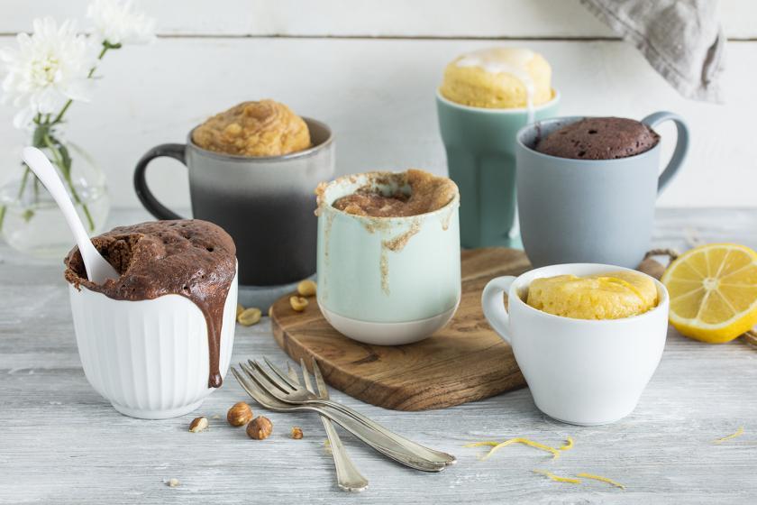 Sechs verschiedene Tassenkuchen auf einem Holzuntergrund angerichtet.