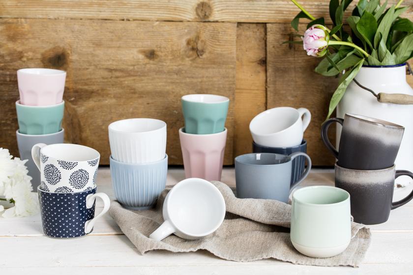 Sechszehn Tassen in verschiedener Größe stehen auf einem Holzuntergrund.