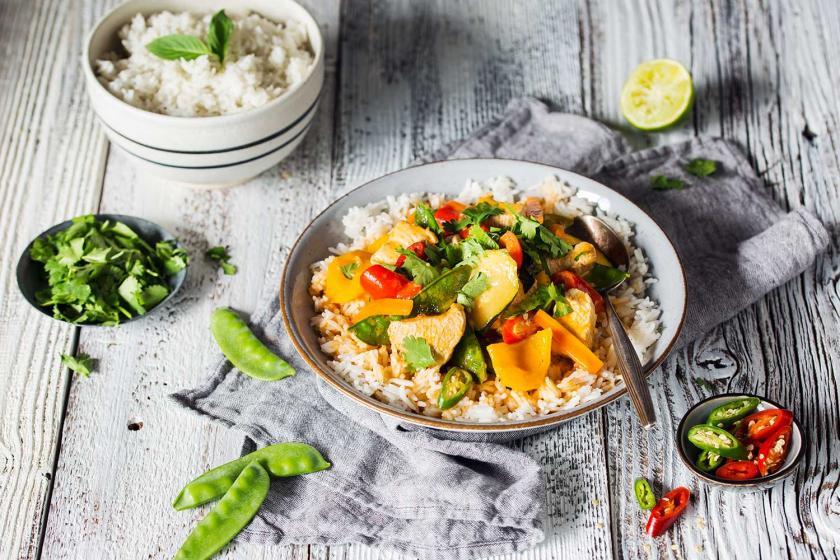Thai Curry mit Reis auf einem Teller angerichtet.