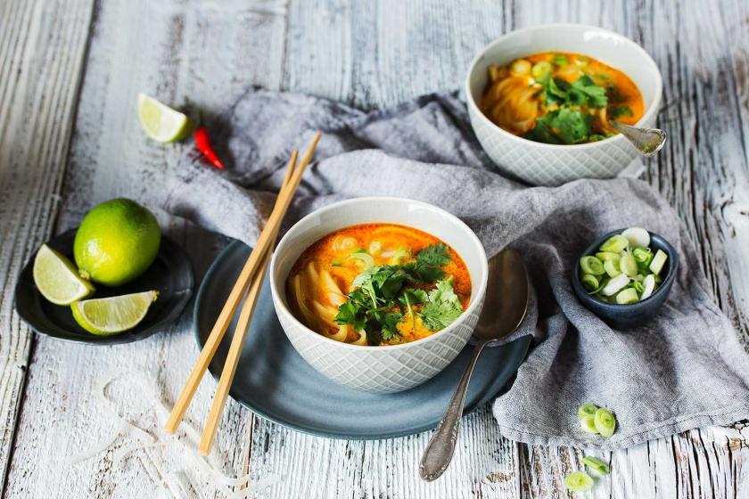 Thai Suppe in einer Schüssel mit Stäbchen und Toppings angerichtet.