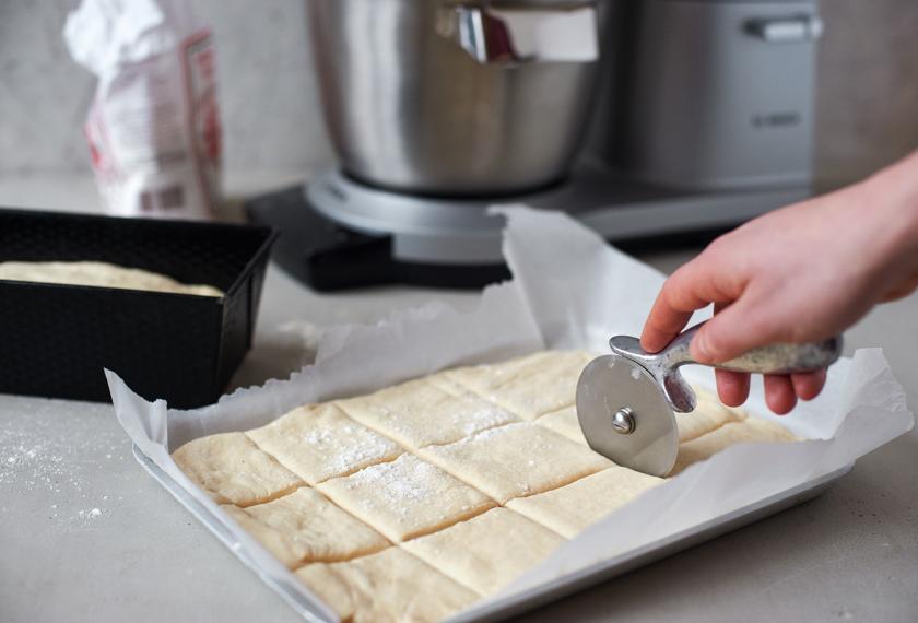 Der Teig von dem Toastbrot Rezept wurde ausgerollt und wird mit einem Pizzaschneider in Quadrate geschnitten.