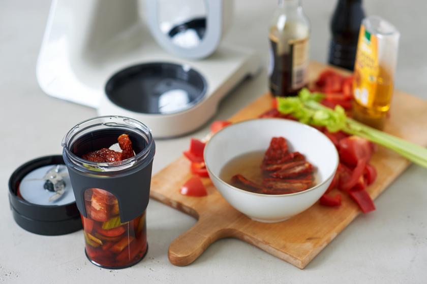 Die Zutaten für den Tomatensmoothie werden in einem Mixer püriert. Daneben Zutaten auf einem Holzbrett.