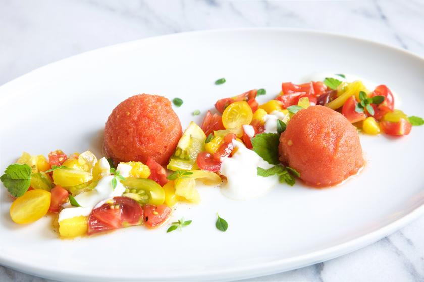Tomatensorbet mit Salat auf einem Teller angerichtet.