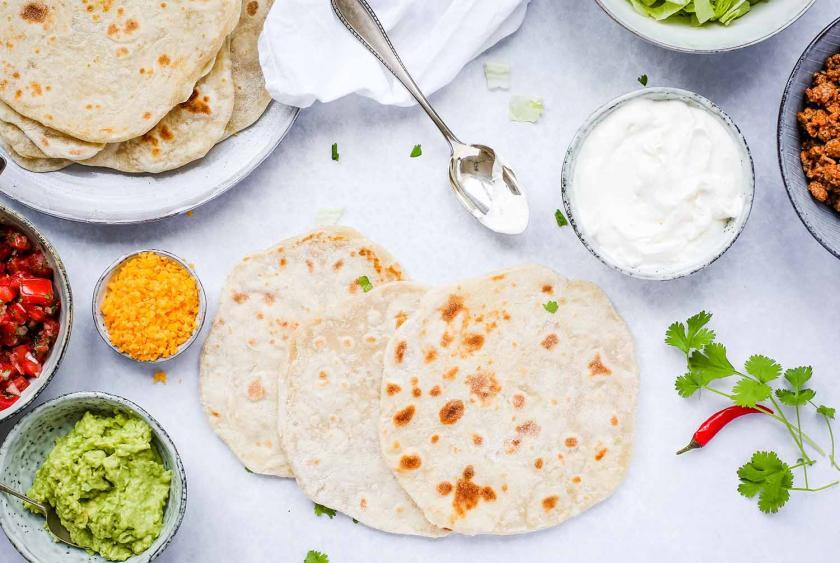 Ungefüllte Tortillas für Tortillas selber machen liegen auf einem Tisch. Drumherum die Zutaten zum Befüllen.