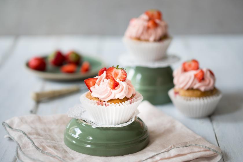 Vegane Cupcakes mit Erdbeerfrosting im Papierförmchen auf einer umgedrehten Schale.