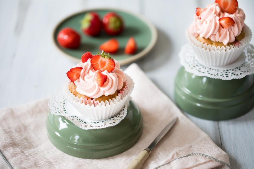 Vegane Erdbeercupcakes mit Frostig und frischen Erdbeeren auf einer umgedrehten Schale serviert.