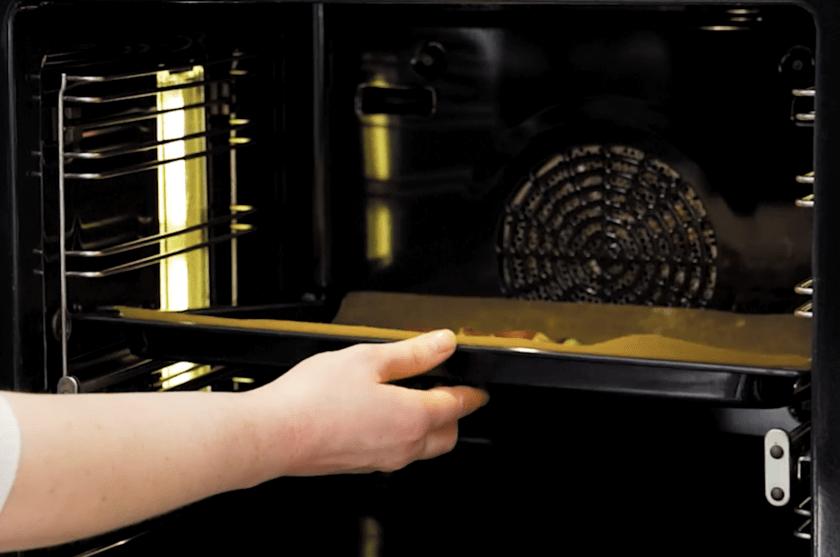 Flammkuchen in den Ofen schieben.