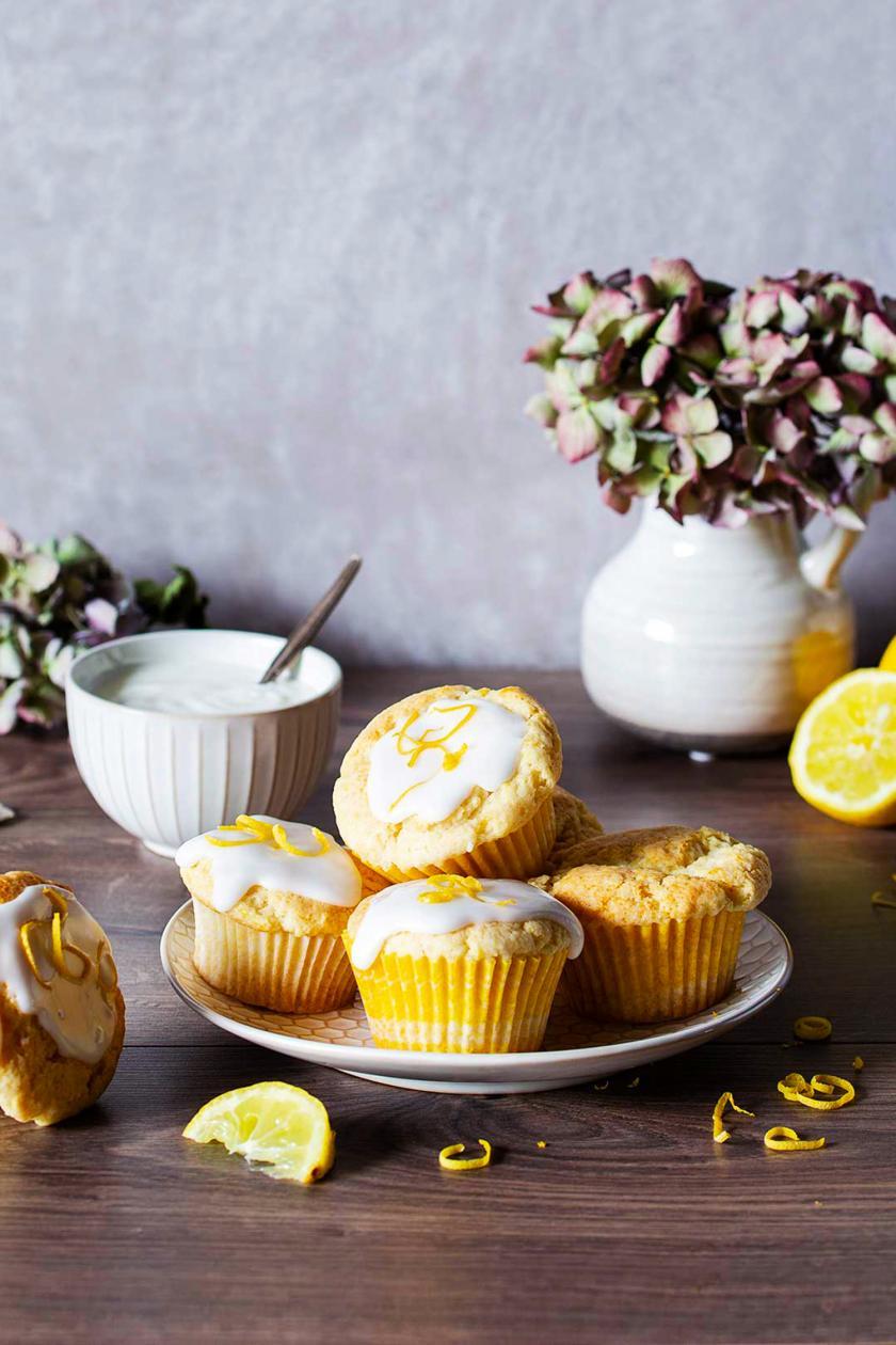 Mehrere vegane Zitronenmuffins auf einem Teller mit Zitronen und Blumen.