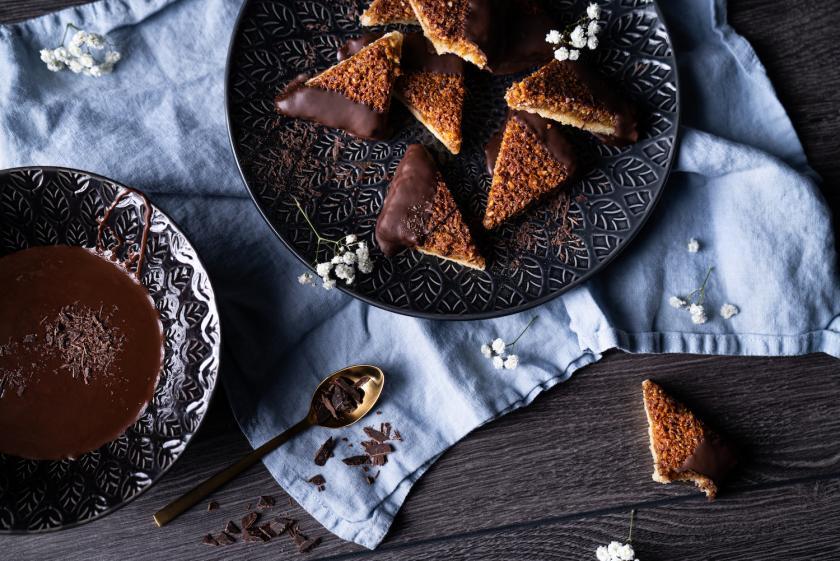 Veagane Nussecken auf schwarzen Tellern in dunklem Setting.
