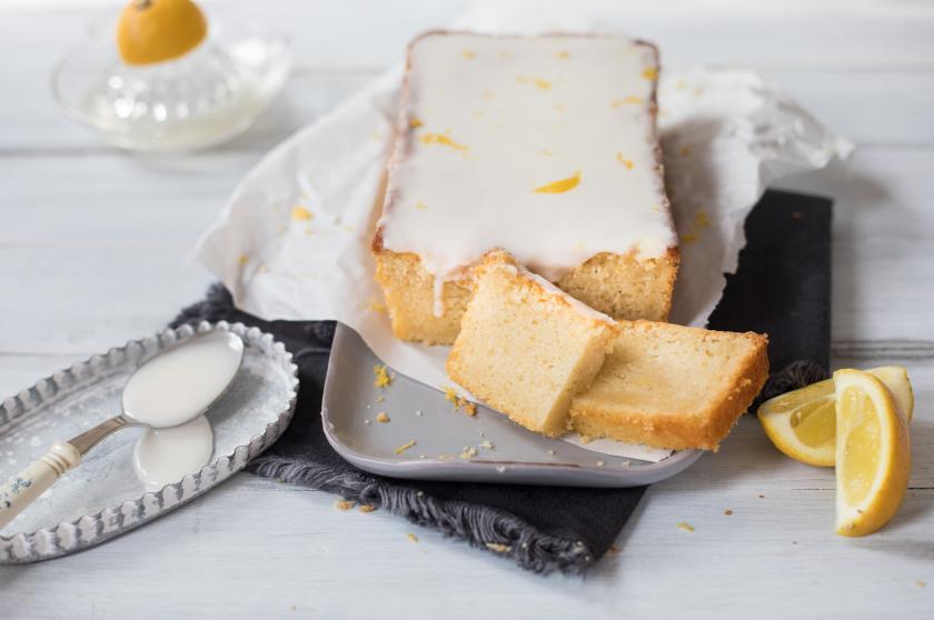 Veganer Zitronenkuchen mit Glasur aufgeschnitten und auf einem Teller angerichtet.