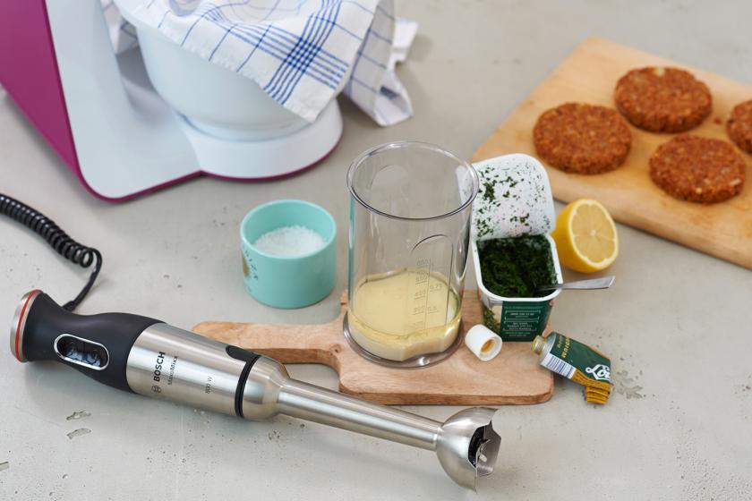 Die Zutaten für die vegetarischer Burger Rempulade samt Pürierstab liegen auf einem Tisch.
