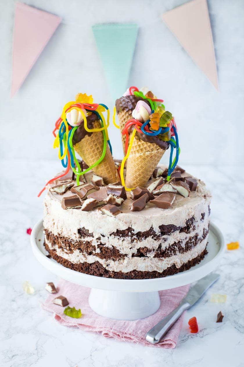 Schokoladentorte mit Frosting und drei gefüllten Eiswaffeln mit Gummibärchen.