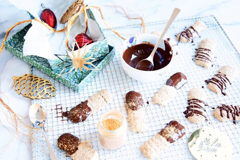 Weihnachtliche Katzenzungen auf einem Tisch verteilt mit Schokolade in der Mitte.