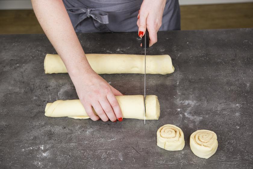 Der Teig für die Zimtschnecken wurde zusammengerollt und wird in Stücke geschnitten.