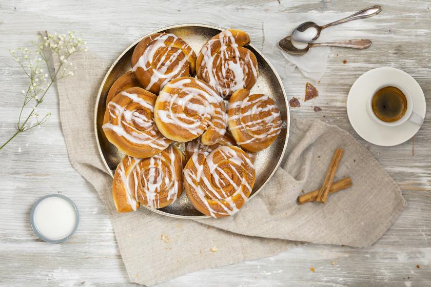 Zimtschnecken mit Zuckerguss liegen auf einem Teller. Daneben eine Tasse Kaffee.