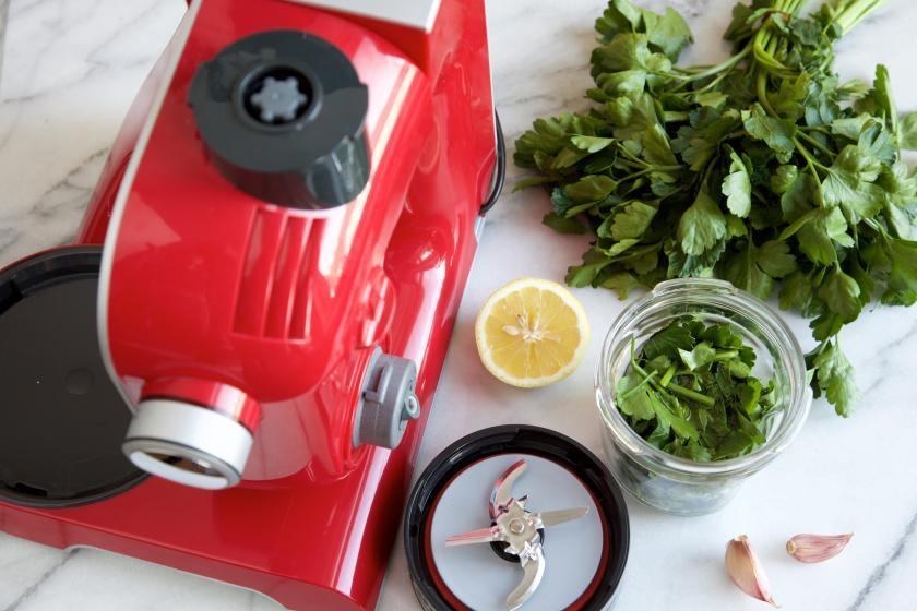 Kräuter werden in einer Küchenmaschine für das Hähnchen-Spargel-Päckchen zerkleinert.