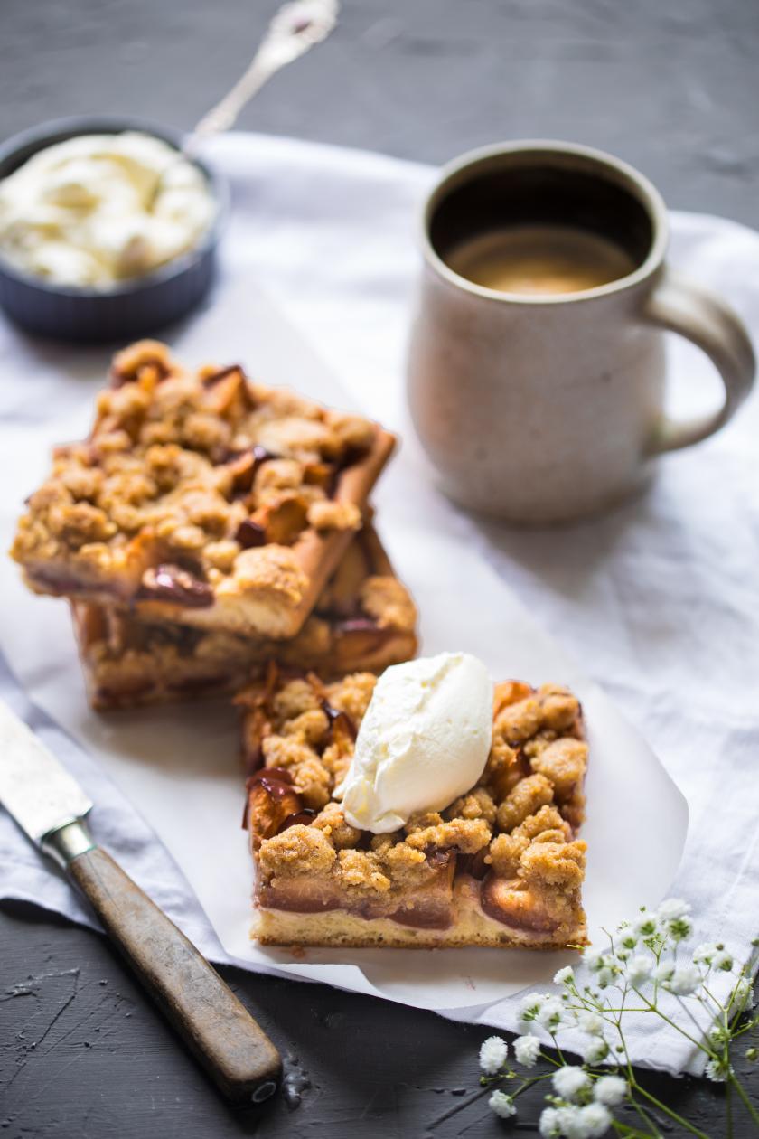 Mehrere Stücke Zwetschgenkuchen mit Nussstreusel zu Kaffee angerichtet.