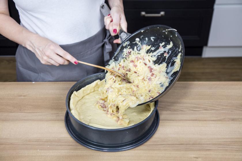 Die Füllung für den Zwiebelkuchen wird aus einer Pfanne auf den Hefeboden gegeben.