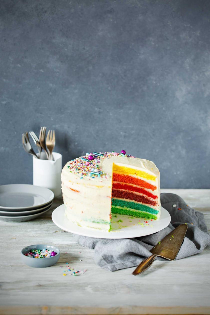 Regenbogenkuchen angeschnitten auf einer Etagere.