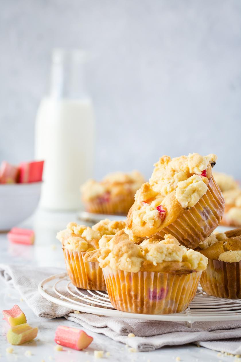 Vier Rhabarber-Muffins aufeinandergestapelt mit Buttermilch im Hintergrund.