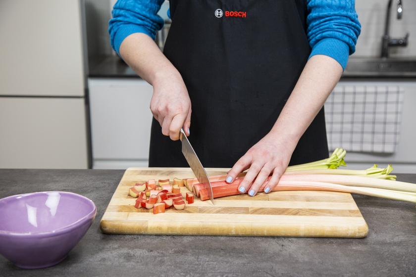 Für den Rhabarberkuchen mit Baiser wird Rhabarber in Stücke geschnitten.