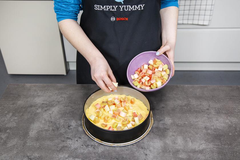 Für den Rhabarberkuchen mit Baiser wird Rhababrber auf den Teigboden in der Springform verteilt.