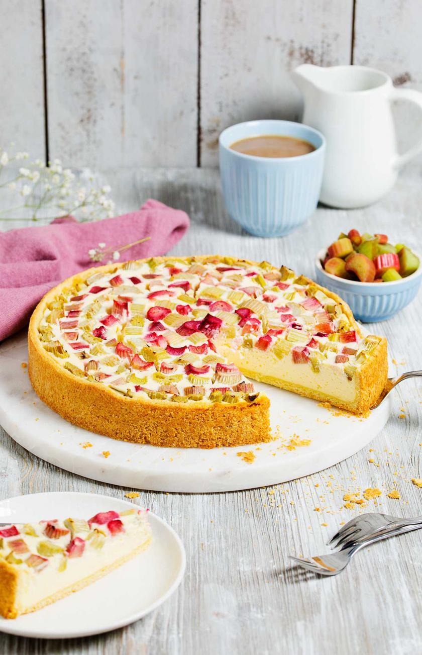 Rhabarberkuchen mit Quark liegt auf einer Kuchenplatte und steht auf einem gedeckten Tisch.