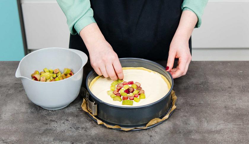 Die Masse des Rhabarberkuchen mit Quark wird mit Rhabarberstücken belegt.