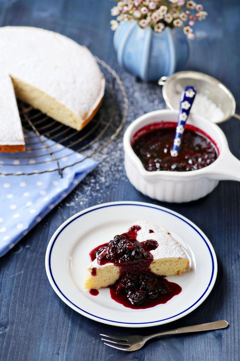 Ein Stück Ricottakuchen auf einem Teller mit Beerensoße garniert, im Hintergrund der restliche Kuchen.