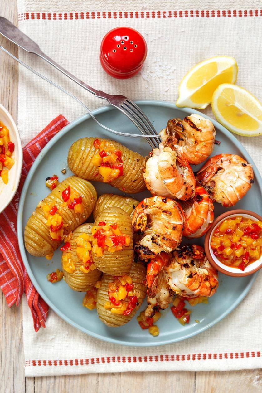 Riesengarnelen mit Chutney und Kartoffeln auf einem Teller.