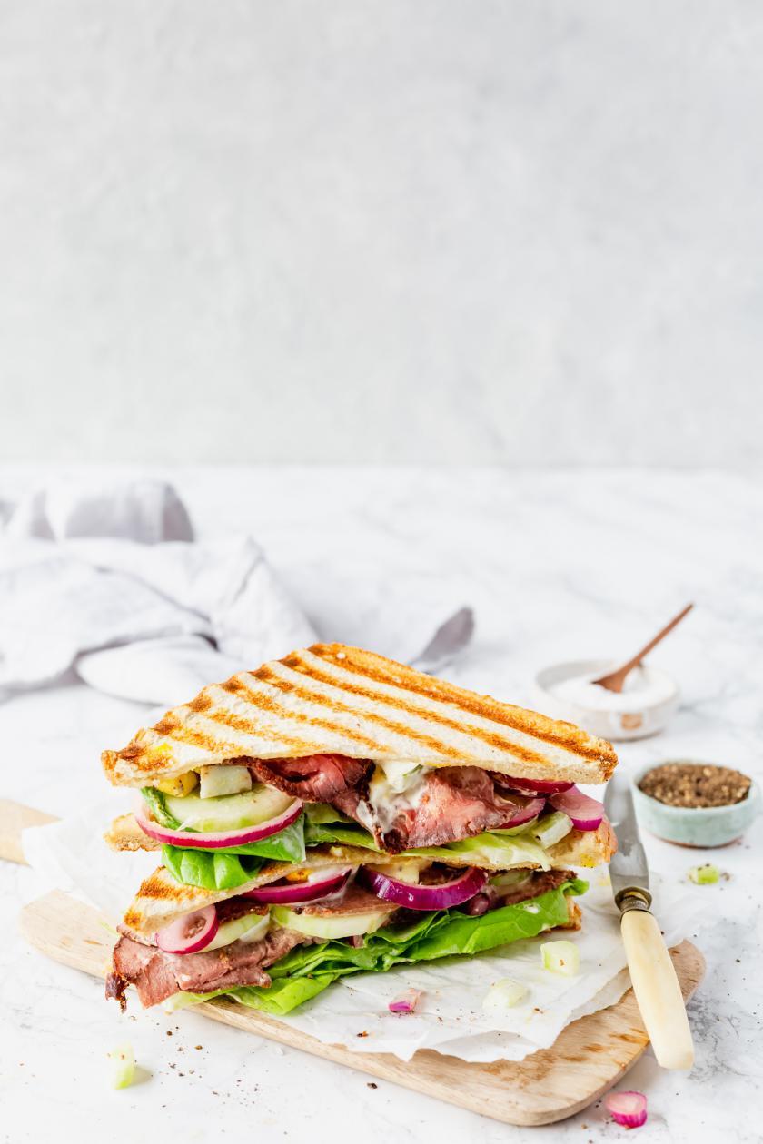 Angeschnittenes Roastbeef-Sandwich auf Holzbrett.