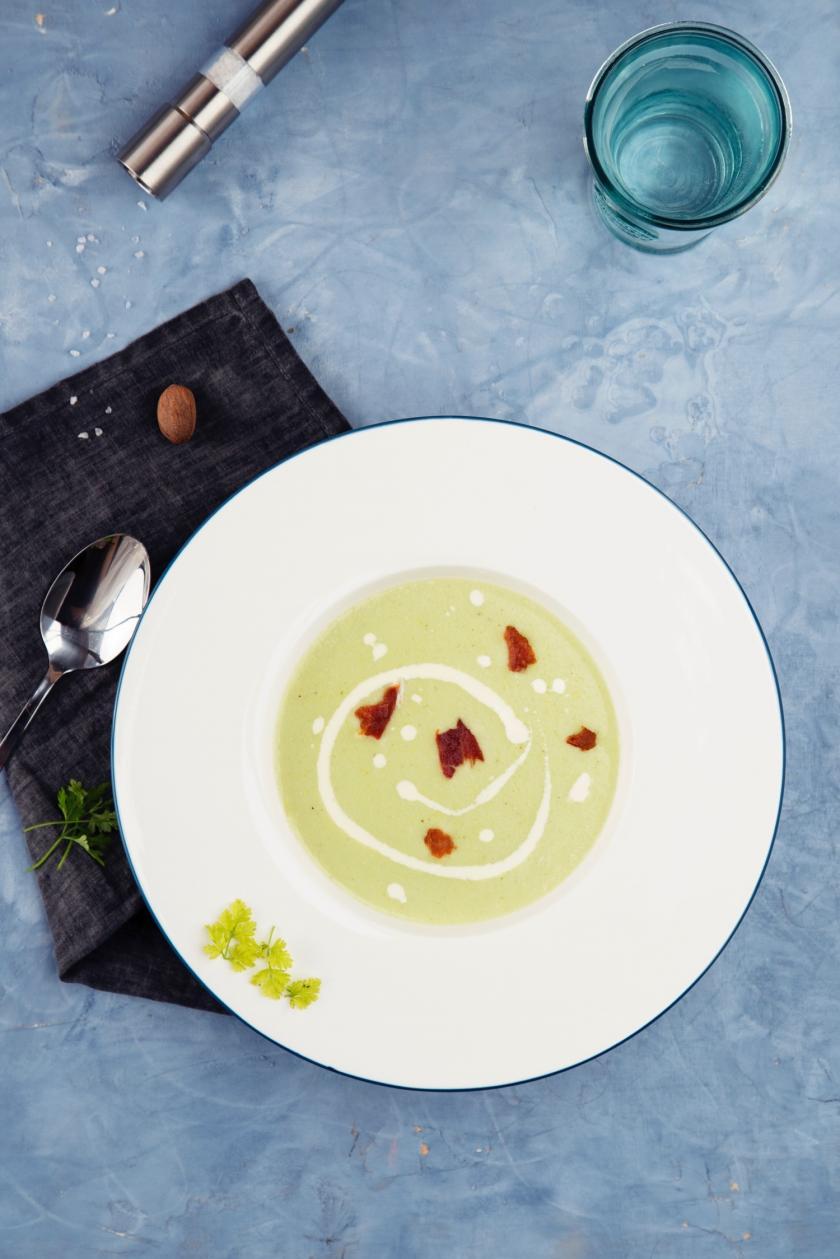 Rosenkohlcremesuppe in weißem Teller auf blauem Tisch