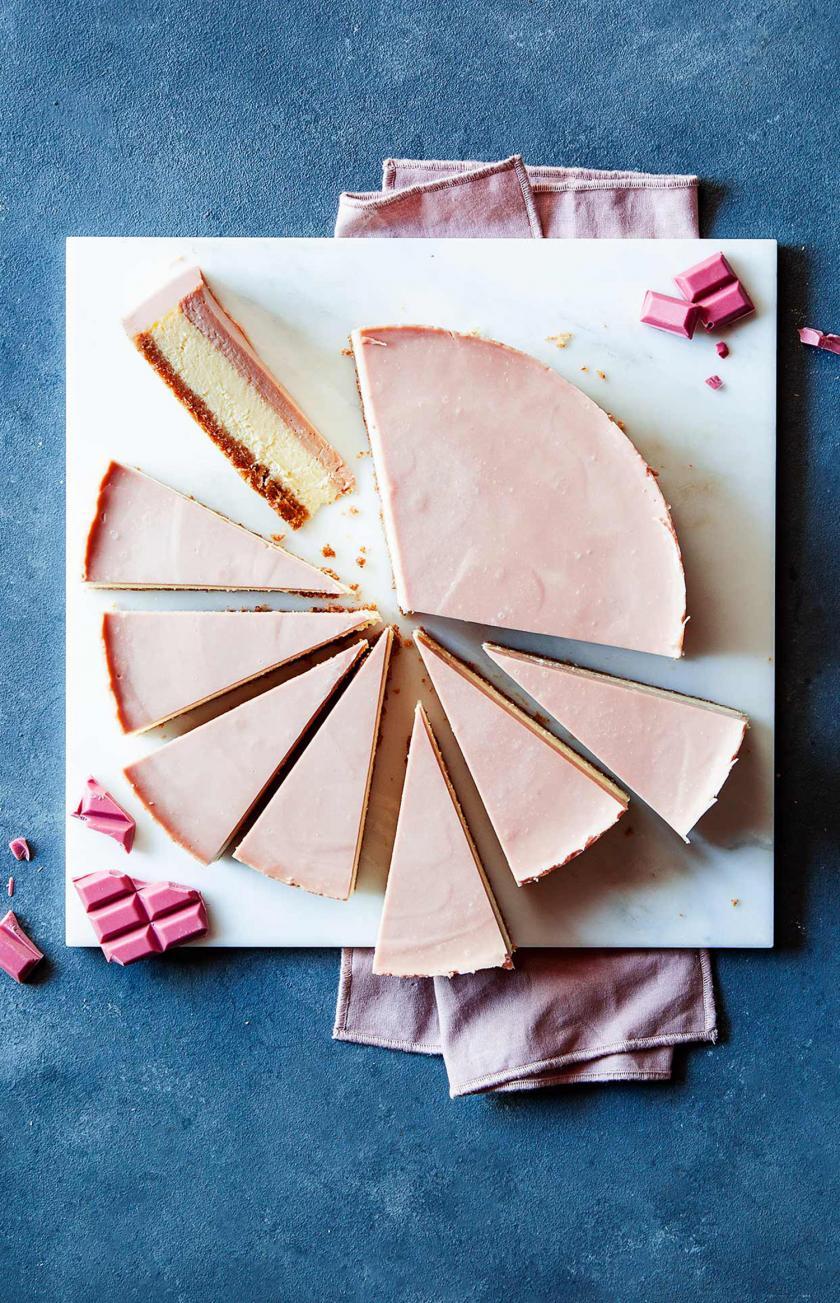 Ruby Chocolate Cheesecake in Stücke geschnitten auf einer Kuchenplatte.