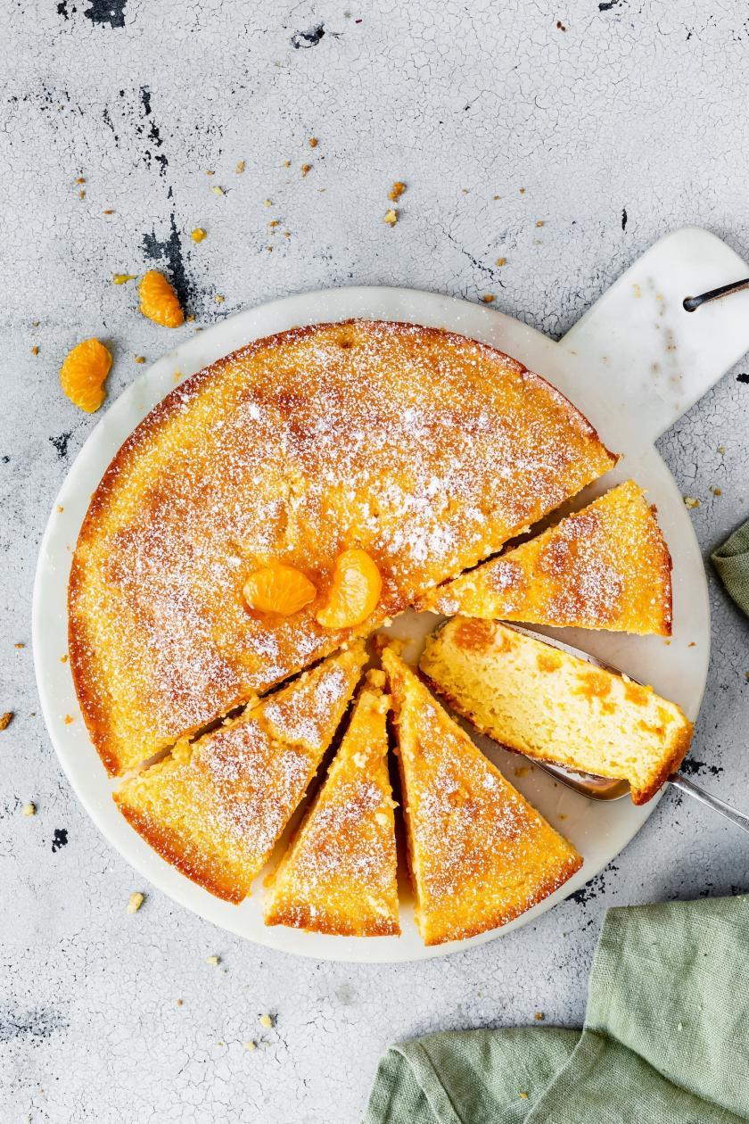 Rührkuchen mit Mandarinen angeschnitten auf einer Kuchenplatte.