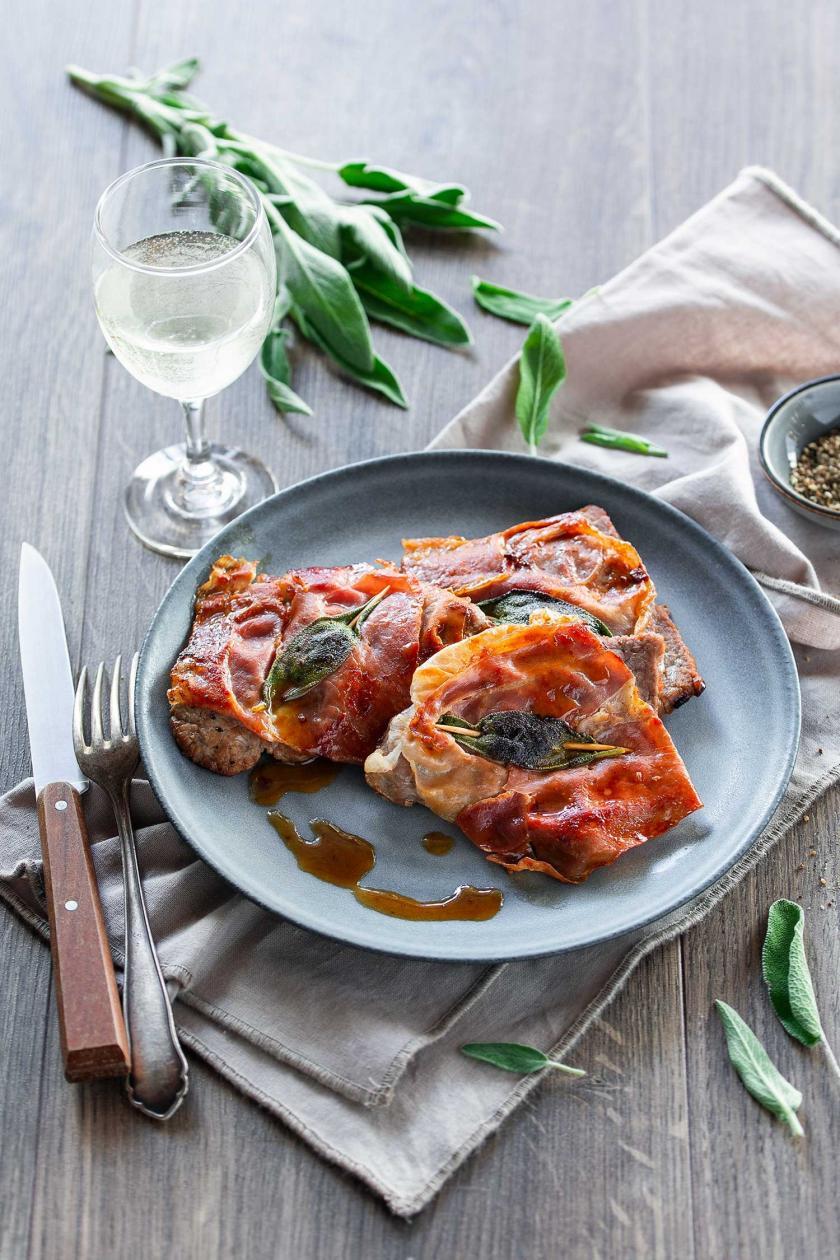 Saltimbocca alla romana auf einem Teller angerichtet mit Soße.