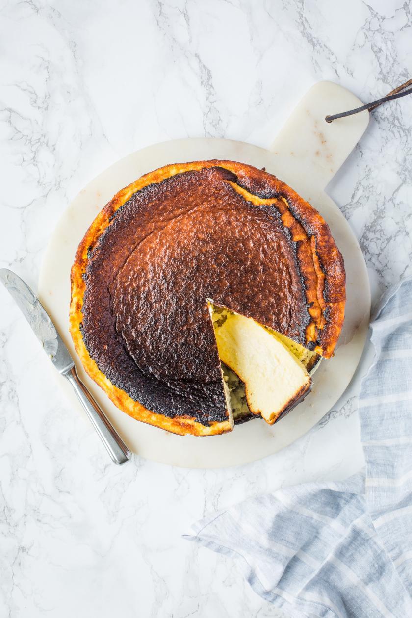 Angeschnittener San Sebastian Cheesecake auf Marmortisch.