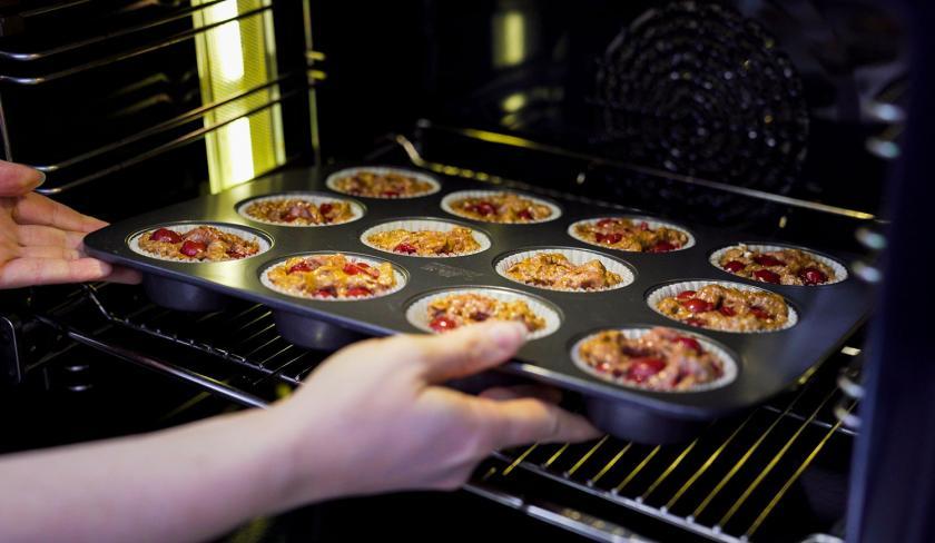 Ein Blech mit Schoko-Kirsch-Muffins wird in den Backofen geschoben.