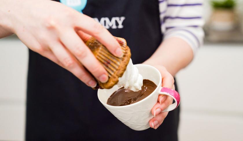 Ein Schoko-Kirsch-Muffins wird kopfüber in flüssige Schokolade getaucht.
